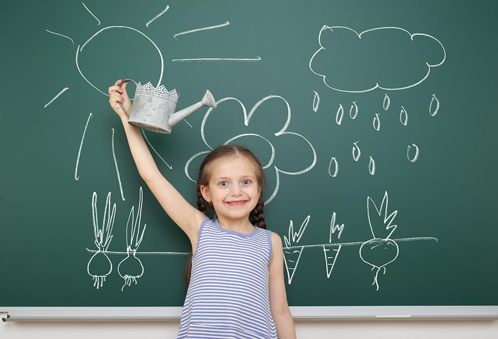 Kind steht an der Tafel, Gartenzeichnung auf Tafel